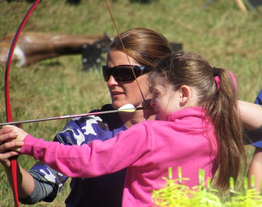 Renee Haers, of Phelps, N.Y., coach of the Heritage Raptors youth archery program, helps a youngster shoot a bow and arrow during the 2015 Southern Tier Outdoor Show in Bath.