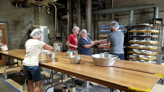 Bakers at Resurrection Catholic Church prepare Caramel Pecan Yum Yums, risen yeast rolls topped with sweet caramel sauce and nuts, on Sunday, Oct. 6, 2019.