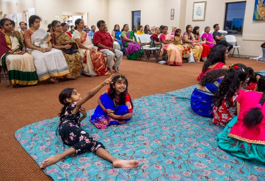 Shrika Reddy of Newburgh, 6, left, points something out to her friend Tharunika Valluru of Newburgh, 5, during Durga Puja at the Tri-State Hindu Temple, Newburgh, Sunday night, Oct. 6, 2019.