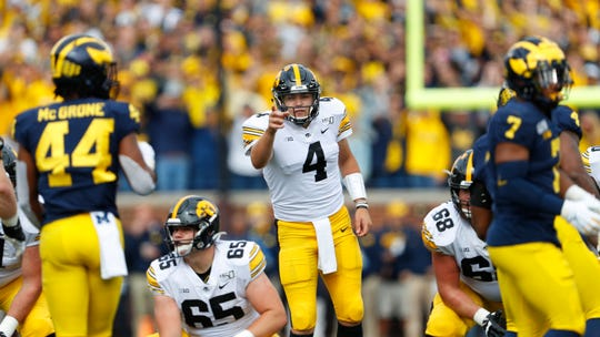 Iowa quarterback Nate Stanley sizes up the line of scrimmage as Michigan linebacker Cameron McGrone (44) lurks. The Hawkeyes continuously failed to account for McGrone in pass protection.