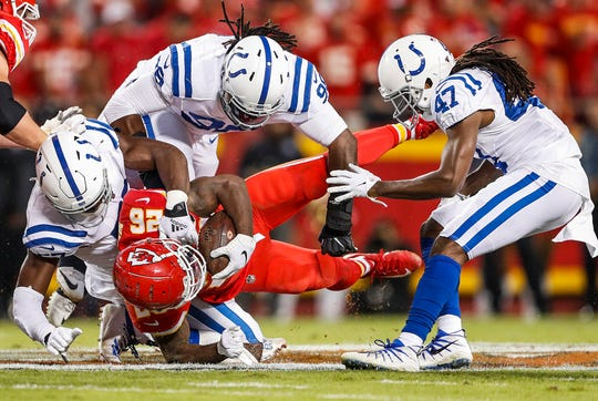Indianapolis Colts defensive end Kemoko Turay (57), defensive end Justin Houston (99) and cornerback Shakial Taylor (47) tackle Kansas City Chiefs running back Damien Williams (26) during the first quarter of their game at Arrowhead Stadium in Kansas City, Mo., on Sunday, Oct. 6, 2019.