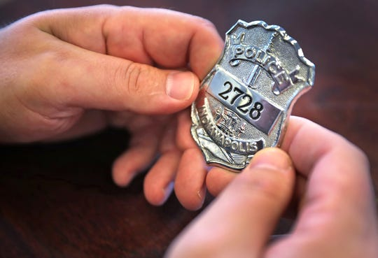 """IMPD Officer Eric Strange shows his old IPD badge on Sept. 27, 2019. He was the officer who took the guns from Kenneth Anderson just months before Anderson went on a shooting spree that claimed the life of Officer Timothy """"Jake"""" Laird, Anderson's mother, and left multiple officers wounded. After years of silence, Strange has spoken out about the incident. He wants to fight for the establishment of red flag laws nationwide to prevent incidents like this."""