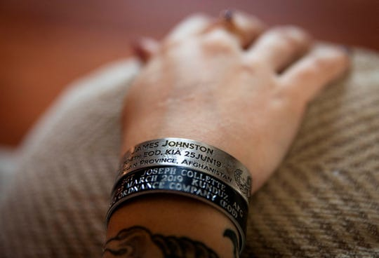 Krista Johnson wears a memorial bracelet for her husband, Sgt. James Johnston, who was killed in Afghanistan in June, as she sits in her childhood home in Trumansburg, N.Y., Saturday, Aug. 31, 2019. As the nation's longest war marks the end of its 18th year, Krista returns to her tiny hometown for two milestones: In one weekend in the local American Legion hall, she joins hundreds to pay tribute to her husband with a 21-gun salute, TAPS and remembrances. A day later, she returns for a baby shower, celebrating the impending birth of their daughter he didn't live to see. (AP Photo/David Goldman)