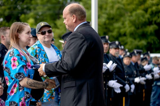 Krista Johnston, left, is presented with a U.S. flag that flew over the U.S. Capitol by Rep. Tom Reed, R-N.Y, during a memorial service for her husband, Sgt. James Johnston, who was killed in Afghanistan in June. in Trumansburg, N.Y., Saturday, Aug. 31, 2019. (AP Photo/David Goldman)