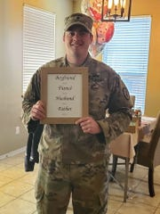 """This March 20, 2019 photo, provided by Krista Johnston, shows her husband, Sgt. James Johnston, 24, with the sign she presented him announcing she was pregnant in Copperas Cove, Texas. When Krista delivered the news, tears rolled down his cheeks. """"It was the first time I'd see him cry in the seven years we'd been together,"""" she recalls. She cried, too. The next morning, he headed to war. (Krista Johnston via AP)"""