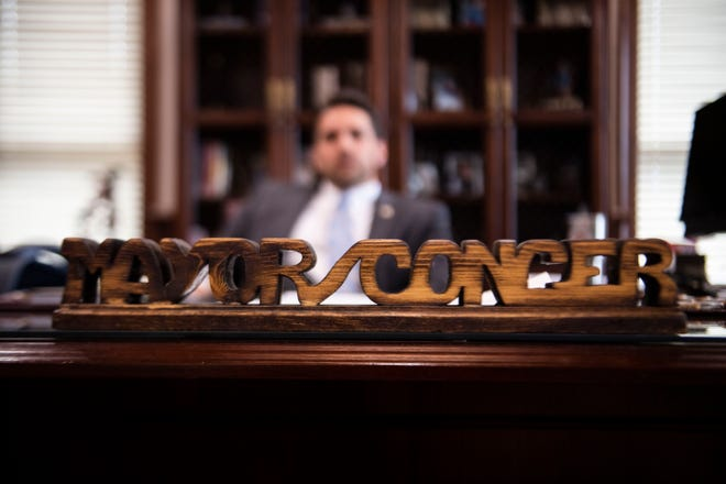 Jackson Mayor Scott Conger sits behind a wooden 'Mayor Conger' signed his grandfather, Bob Conger, had made when was mayor of Jackson in City Hall in Jackson, Tenn. on Monday, Oct. 7, 2019.