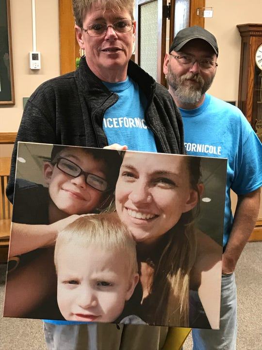 Cheryl Samuels, with husband Mark Samuels, holds a picture of her daughter Nicole Bowen and her grandchildren, Korbin and Riley, before a hearing at the Newton County Courthouse in Kentland on Monday, Oct. 7, 2019. Jasmine Parker, one of five people charged in connection to the death of Bowen, pleaded guilty Monday to assisting a criminal and was sentenced to five years in prison.