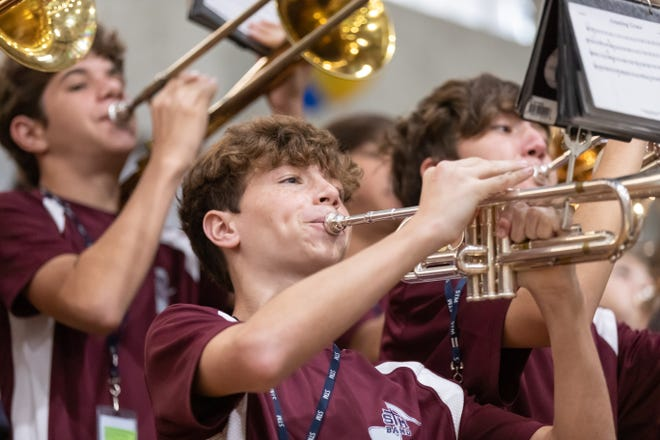 """St. Thomas More Catholic High's Cougar Band performs Friday, Oct. 4, at the 24th annual academic pep rally. This year's theme was decades because """"good grades are timeless."""""""