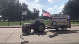 """A supporter for gubernatorial candidate Ralph Abraham rides on a tractor with """"Abraham for governor"""" sign as he passes by saying """"vote for Abraham."""""""
