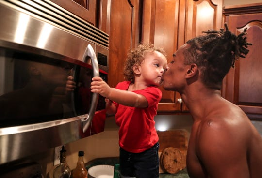 """Kingston Lukes kisses father Marion while the 17-year-old fixes dinner after practice. """"I wouldn't say I was disappointed. I was shocked,"""" said Nichole Lukes, Marion's mother. """"I just feel like he was really young when it happened. Having a baby is a lot of responsibilities."""""""