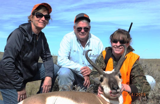 Madysen Leiterman shows her pronghorn antelope she shot near Casper, Wyoming, as her grandparents, Steve and Karen Olson, look on. Madysen made a perfect 145-yard shot taking out both lungs. The antelope sported 14-inch prongs.
