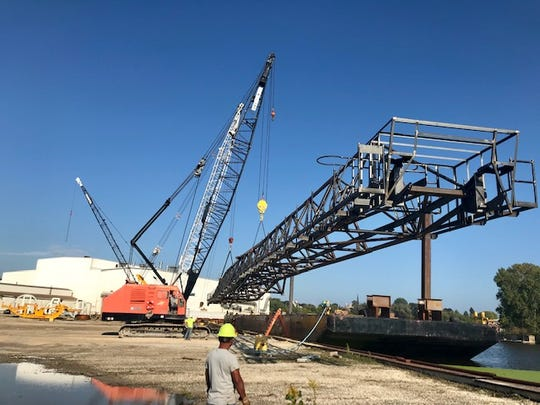 Workers at Manitowoc's Broadwind help load a large boom onto a barge to Sturgeon Bay