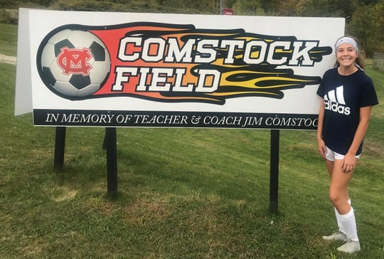 Mansfield Christian's Olivia Bekeleski stands in front of the Comstock Field sign dedicated to her late grandfather, Jim Comstock. She is the only grandchild who plays soccer.