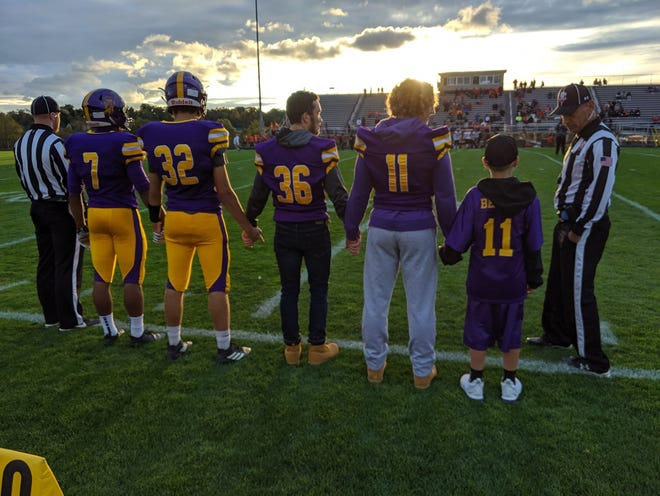 Evan Slaton (far right) was an honorary captain during the Lexington vs Mansfield Senior game in Week 6.