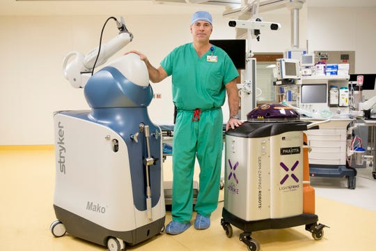 Dr. Matthew Bernhard stands with Mako, the new robot that has helped him perform more than 700 knee and hip replacements at OhioHealth Mansfield Hospital.