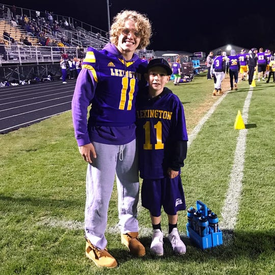 Evan Slaton poses for a picture with his favorite Lexington Minuteman football player Kaydan Berry during a game against Mansfield Senior last week.