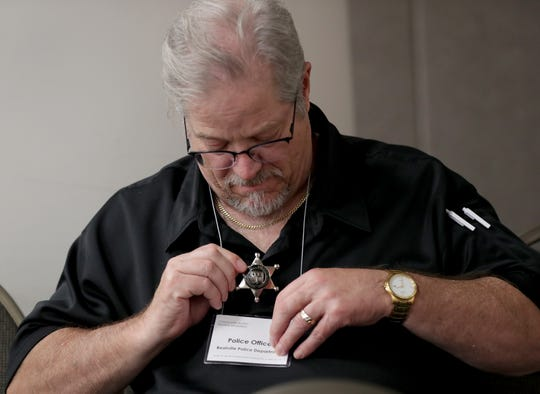 Jim Guldan, a direct service provider for the Social Development Commission, plays a police officer from Realville who  puts on his badge in case any mock arrests need to be made at the 2019 Summit on Poverty.