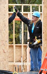Trisha Yearwood and Tennessean columnist Brad Schmitt high five while working on a Habitat for Humanity home on Monday.
