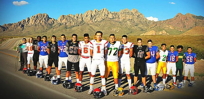 Players from the 2011-2014 Las Cruces Thunder youth football team pose for a reunion photo in their respective high school uniforms.