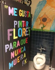 "A student-painted mural in a Lynn Community Middle School bathroom. The quotation on the stall door is from the artist Frida Kahlo, and in English, it translates to, ""I like to paint flowers so that they never die."" The community school model is one the school district and city plan to replicate at other sites."