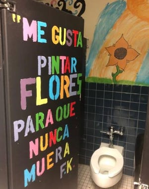 "A student-painted mural in a Lynn Community Middle School bathroom. The quotation on the stall door is from the artist Frida Kahlo, and in English, it translates to, ""I like to paint flowers so that they never die."""
