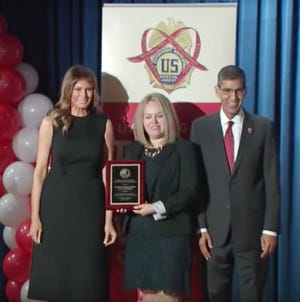 Marisol Diaz, director for prevention and community collaborations for the  Center For Health Innovation, center, receives an award from First Lady of the United States Melania Trump, left, and  Drug Enforcement Administration Acting Administrator Uttam Dhillon, in Washington D.C. on Monday Oct. 7, 2019, for the National Red Ribbon Rally.