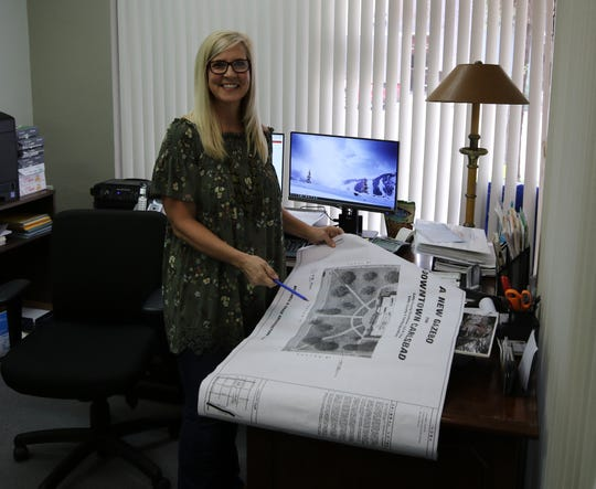 Karla Hamel, Carlsbad MainStreet director, shows off plans for a new gazebo set for the Eddy County Courthouse lawn.