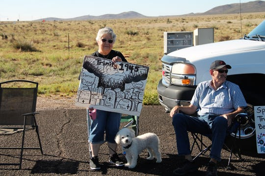 Rosalie Cordova stands with her sign near the turn-off for the Trinity Site Open House Oct. 5. White Sands Missile Range held its biannual Trinity Site Open House Saturday, Oct. 5. The event drew a large crowd trying to get in and a group of protesters from the Tularosa Basin Downwinders Consortium.