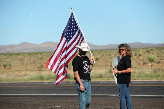 Tina Cordova, right, stands with her sign on Highway 380 near the turn-off for the Trinity Site Open House Oct. 5. White Sands Missile Range held its biannual Trinity Site Open House Saturday, Oct. 5. The event drew a large crowd trying to get in and a group of protesters from the Tularosa Basin Downwinders Consortium.