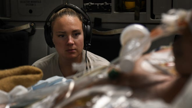 Capt. Natasha Cardinal, 86th Aeromedical Evacuation Squadron critical care nurse, monitors her patient during a flight from Bagram Airfield,  Afghanistan to San Antonio, Texas, Aug. 18, 2019. Critical care air transport teams are rapidly deployable teams consisting of a physician,  critical care nurse and a respiratory therapist who provide a mobile intensive care unit for complex, critically wounded patients.