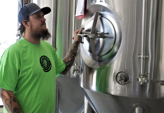 Brandon Beard examines the brewing equipment at the Lauter Haus Brewing Company in Farmington.
