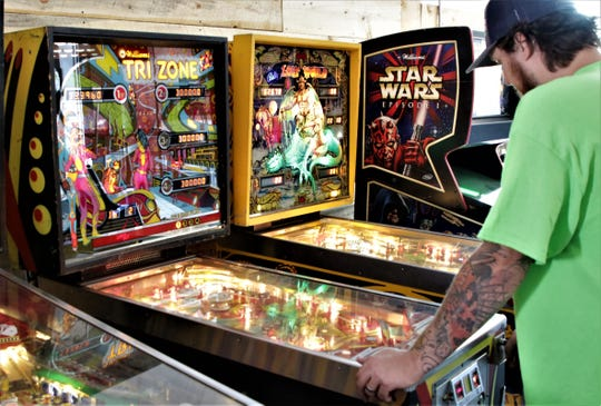 Brandon Beard tries his luck on one of the vintage pinball machines in the arcade at the Lauter Haus Brewing Company.