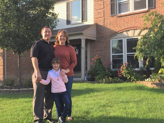 Canton's Gudith family stand in the front yard of their home that they've had to vacate temporarily due to a health-harming case of an invisible mold.