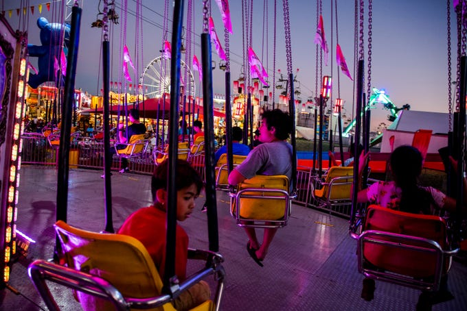 "Children wait in the chair swing ride they just rode at the Arizona State Fair in Phoenix on Oct. 6, 2019.&nbsp;<strong>STATE FAIR 2019:</strong> <a href=""https://www.azcentral.com/story/entertainment/events/2019/09/25/arizona-state-fair-2019-dates-prices-discounts-deals-wristbands-concerts-events-hours-food/2347028001/"">Deals, what&#39;s new and all you need to know</a>&nbsp;