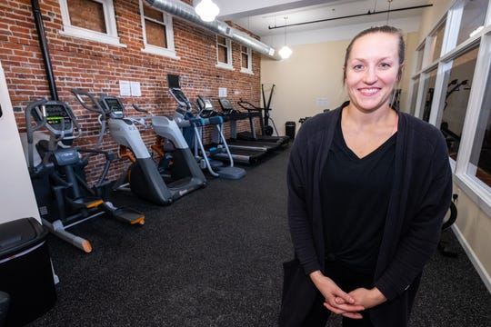 Emily Lelito poses for a photo inside Afterburn Fitness Club Monday, Oct. 7, 2019. Emily opened the gym on the first floor of the Ballentine building in Port Huron with her husband Tim.