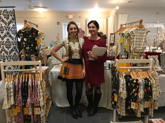 Eva, left, and Robin Hayes, co-founders of Lucky Bug Clothing Company, are shown at a holiday craft market with their Lucky Bug wares.