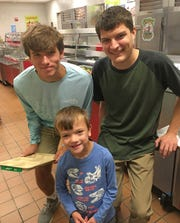 Southern Elementary kindergarten student Nolan Kloster is shown in the school cafeteria with Susquehannock High School seniors Greyson Murray (holding the adaptive food tray) and Nathan Driscoll. The third senior working on the project, Saige McKenzie, was not available for the photograph.