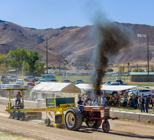 An antique Farmall 460 tractor pulls the sled in the tractor pull competition.