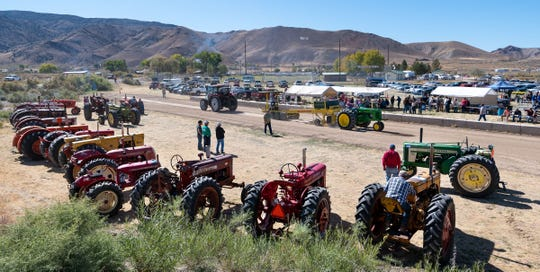 Numerous antique tractors line the edge of the tractor pull strip.