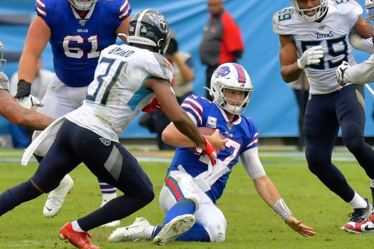 Buffalo Bills quarterback Josh Allen (17) slides down to avoid the tackle by Tennessee Titans free safety Kevin Byard (31) during the second half at Nissan Stadium on Sunday.