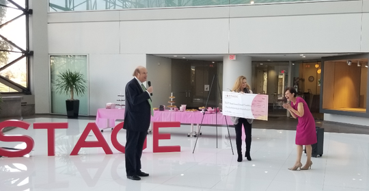 Michael Glazer, CEO and President of Stage Stores, presents Myra Biblowit, President and CEO of Breast Cancer Research Foundation, a $375,000 toward breast cancer research.