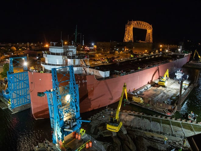 The 610-foot William A. Irvin makes its way through the opening of the Minnesota Slip pedestrian drawbridge early on Sept. 22, 2018 in Duluth. The Irvin had to be moved out of its home so workers could perform environmental remediation of the slip. The ship returned to its home in the Duluth Harbor on Wednesday evening, successfully maneuvering through the opening with just 7 inches of clearance on either side.