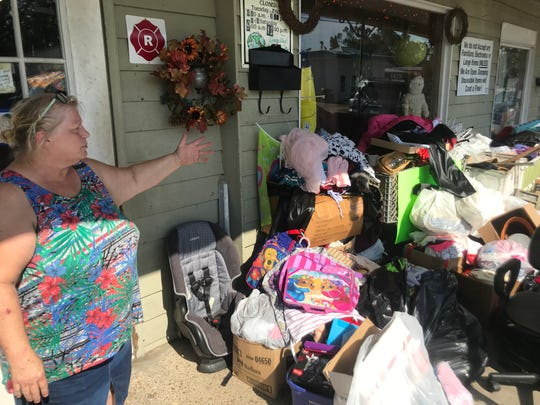 Joanie Ridley, owner of Helping Hands thrift store in Blountstown, shows off the merchandise collected since Hurricane Michael struck a year ago.