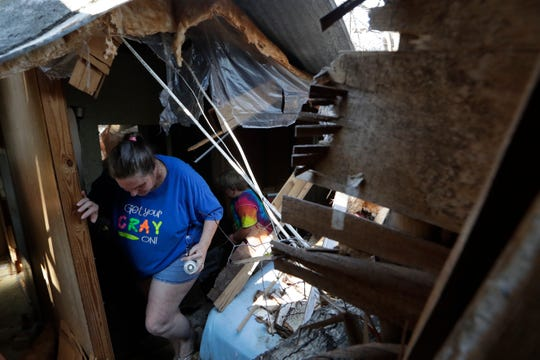 Kaye Elmore ducks under a piece of fallen ceiling that hangs in one of the bedrooms of her home that was destroyed when a tree fell through it during Hurricane Michael last year.