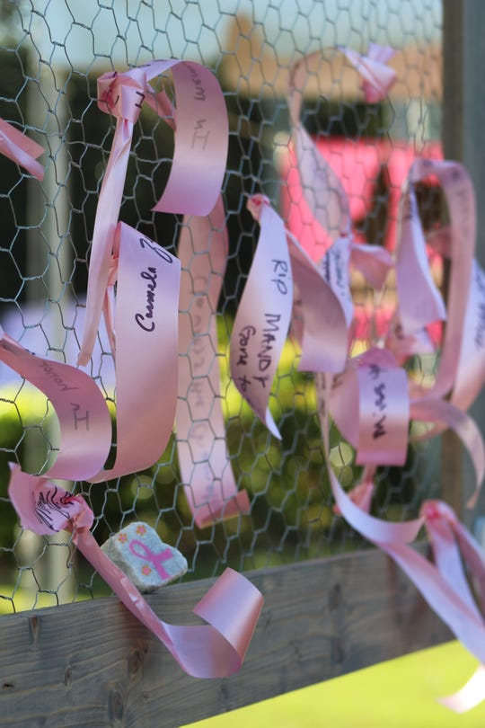 "Making Strides Against Breast Cancer supporters leave expressions of love and admiration on the ""Wall of Hope"" and the names of loved ones are inscribed on pink ribbons tied to a large frame declaring ""Forever In Our Hearts!"""
