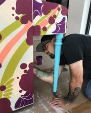Artist Christopher Hurtado is painting an upright piano in preparation for Chalk the Block.