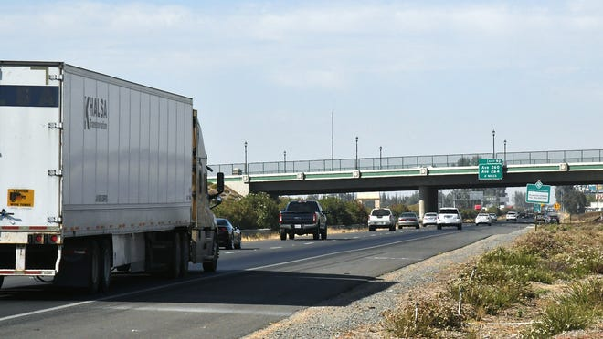 Cars zoom down Highway 99 near the Cartmill Avenue exit in Tulare on Monday afternoon. Plans to widen the freeway in Tulare and Madera County to six lanes have been canceled by the California Department of Transportation.