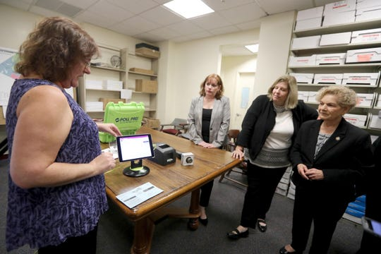 "Brenda Mone, Rockland County Democratic Election Inspection Coordinator, demonstrates the ""Poll Pad"" Oct. 7, 2019. Beginning with early voting in Rockland County later this month, the electronic device will take the place of the election sign in book that voters have used for decades to sign in to vote when arriving at an election site. Looking on was Patricia Giblin and Kristen Zebrowski Stavisky, the two Rockland County's two election commissioners, and assemblywoman Ellen Jaffee."