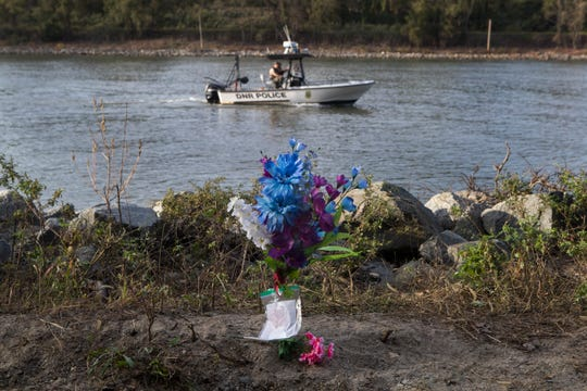 Flowers and a handwritten note of sympathy sit on the edge of the Chesapeake & Delaware Canal as a DNREC Fish & Wildlife Natural Resources Police boat searches for 6-year-old Ethan Lindsey on Monday afternoon. Lindsey's body was found Thursday morning.