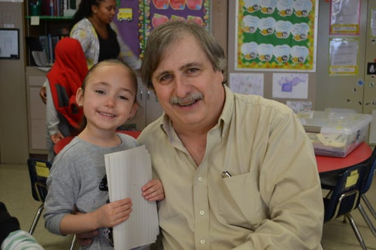 Jeffrey Benatti, executive director of New Castle County Head Start, with a student.